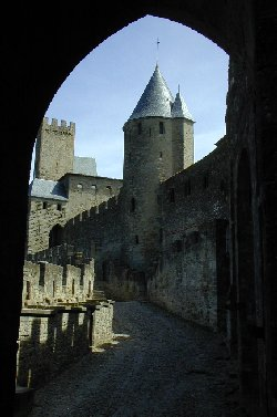 A huge stone archway frames one of the spires of Carcassonne Cité
